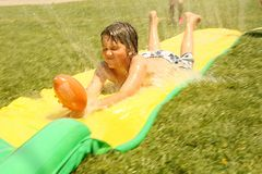 Childhood Water Fun. Young Child Enjoying a Water Slide in Summer Stock Images