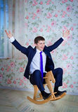 Childish businessman with toy horse Stock Images