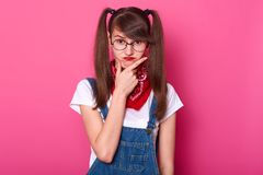Childish charismatic young lady puts her hand on face, thinking over her plans, makes frowny face. Funny girl with bangs and long. Pigtails stands straight royalty free stock images