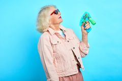 Childish crazy funny granny holding a toy pistol , playing with it stock photography