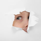 Childish eye looking from hole in paper Royalty Free Stock Photos