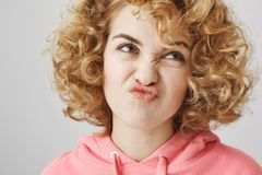 Childish feminine caucasian curly-haired woman making faces and looking up, expressing dislike or unwillingness to do. Something, standing over gray background Royalty Free Stock Photo