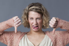 Childish girl expressing disgust,disagreement and dislike with thumbs down Royalty Free Stock Image