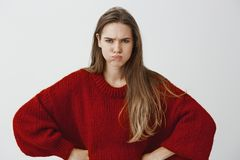 Childish girlfriend wants attention. Portrait of displeased offended european woman in red loose sweater, holding hands. On hips, sulking and frowning, arguing royalty free stock photos