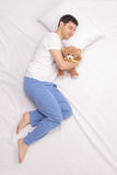 Childish guy sleeping with a teddy bear Royalty Free Stock Photography