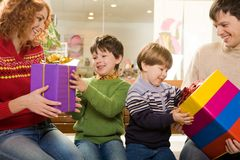 Childish joy. Photo of surprised children being given wonderful gifts by their parents Royalty Free Stock Image