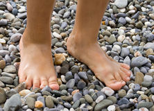 Childish legs on pebble Royalty Free Stock Photos