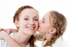 Childish love. Portrait of pretty girl kissing her mother Stock Images