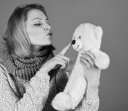 Childish mood concept. Woman holds teddy bear playing with his nose on red. Background. Lady with blond hair looks at cute toy bear. Girl with tender face plays stock photo