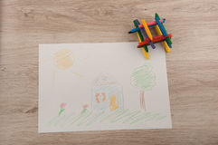 Childish picture and color pencils on wooden table Royalty Free Stock Photo