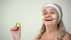 Childish positive lady applying cucumber face mask, optimistic attitude to age royalty free stock image