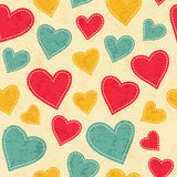 Childish seamless pattern with hearts. Childish seamless pattern with red, yellow and blue hearts. Hand-sewn style elements with white seams. Bright and happy stock illustration