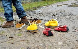 Kid playing with shoes. Childish shoes tied up with a clasp Stock Image