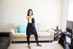 Cute woman enjoying cleaning living room. Childish woman cleaning house while playing with spray and using it as gun in living room Stock Photos