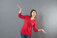 Childish woman using arms and hands like bird to fly like airplane. Hand gesture concept - childish cheerful young woman using her arms and hands like a bird to Royalty Free Stock Photo