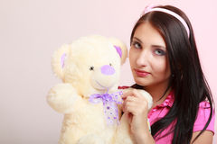 Childish young woman infantile girl in pink hugging teddy bear toy Stock Photos