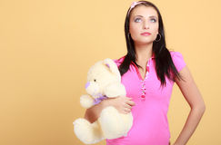 Childish young woman infantile girl in pink hugging teddy bear toy Stock Photo