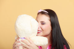 Childish young woman infantile girl in pink hugging teddy bear toy Royalty Free Stock Image