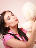 Childish young woman infantile girl in pink kissing teddy bear toy stock images