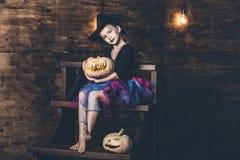 Childl de fille dans le costume de sorcière avec les potirons et la sucrerie chez le Hall Photos stock