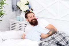 Childlike again. Man adult bearded handsome hipster with childish hairstyle colorful ponytails. Slumber party. Guy. Relaxing in bedroom. Pajamas style. Man in stock photo