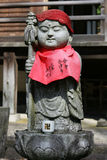 Childlike Buddha. A statue of a childlike Buddha with a cup and buddhist sign on it. The statue has a red clothe around it, this is very common in Japan royalty free stock photo