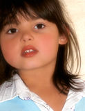 Childlike Softness. Face of a little girl with rosebud shaped lips, brown hair and brown eyes Royalty Free Stock Photos