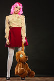Childlike woman and big dog toy. Mental disorder concept. Young childlike woman wearing like puppet doll and big dog toy standing dark black background Stock Images