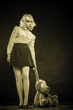 Childlike woman with dog toy on black. Mental disorder concept. Young childlike woman wearing like puppet doll and big dog toy standing dark black background Stock Images