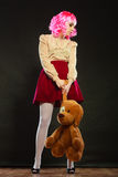 Childlike woman with dog toy on black. Mental disorder concept. Young childlike woman wearing like puppet doll and big dog toy standing dark black background Royalty Free Stock Image