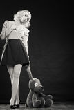 Childlike woman with dog toy on black. Mental disorder concept. Young childlike woman wearing like puppet doll and big dog toy standing black and white photo Royalty Free Stock Photos