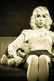 Childlike woman and teddy bear sitting on couch Stock Images