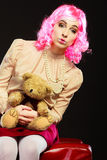 Childlike woman and teddy bear sitting on couch Royalty Free Stock Image