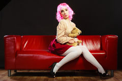 Childlike woman and teddy bear sitting on couch Stock Photography