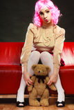 Childlike woman and teddy bear sitting on couch. Mental disorder concept. Young childlike woman wearing like puppet doll sitting with teddy bear toy on red couch Stock Image