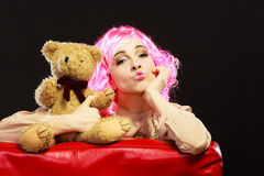 Childlike woman and teddy bear sitting on couch. Mental disorder concept. Young childlike woman wearing like puppet doll sitting with teddy bear toy on red couch Royalty Free Stock Image