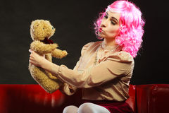 Childlike woman and teddy bear sitting on couch. Mental disorder concept. Young childlike woman wearing like puppet doll sitting with teddy bear toy on red couch Stock Photo
