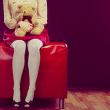 Childlike woman and teddy bear sitting on couch. Mental disorder concept. Young childlike woman wearing like puppet doll sitting with teddy bear toy on red couch Royalty Free Stock Photos