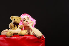 Childlike woman and teddy bear sitting on couch. Mental disorder concept. Young childlike woman wearing like puppet doll sitting with teddy bear toy on red couch Royalty Free Stock Photography