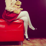 Childlike woman and teddy bear sitting on couch. Mental disorder concept. Young childlike woman wearing like puppet doll sitting with teddy bear toy on red couch Royalty Free Stock Photo