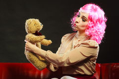 Childlike woman and teddy bear sitting on couch. Mental disorder concept. Young childlike woman wearing like puppet doll sitting with teddy bear toy on red couch Stock Images