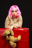 Childlike woman and teddy bear sitting on couch Stock Photo