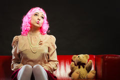 Childlike woman and teddy bear sitting on couch Stock Photos