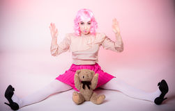Childlike woman with teddy bear toy. Mental disorder concept. Young childlike woman wearing like puppet doll holding teddy bear toy studio shot Royalty Free Stock Photos