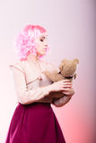 Childlike woman with teddy bear toy. Mental disorder concept. Young childlike woman wearing like puppet doll holding teddy bear toy studio shot Royalty Free Stock Photography