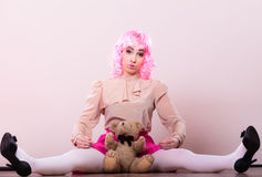 Childlike woman with teddy bear toy. Mental disorder concept. Young childlike woman wearing like puppet doll holding teddy bear toy studio shot Royalty Free Stock Images