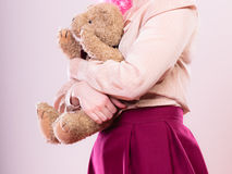 Childlike woman with teddy bear toy. Mental disorder concept. Young childlike woman wearing like puppet doll holding teddy bear toy studio shot Royalty Free Stock Image