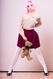 Childlike woman with teddy bear toy. Mental disorder concept. Young childlike woman wearing like puppet doll holding teddy bear toy studio shot Stock Photos
