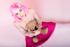 Childlike woman with teddy bear toy. Mental disorder concept. Young childlike woman wearing like puppet doll holding teddy bear toy studio shot Stock Images