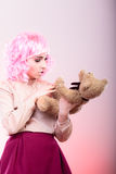 Childlike woman with teddy bear toy. Mental disorder concept. Young childlike woman wearing like puppet doll holding teddy bear toy studio shot Stock Photography